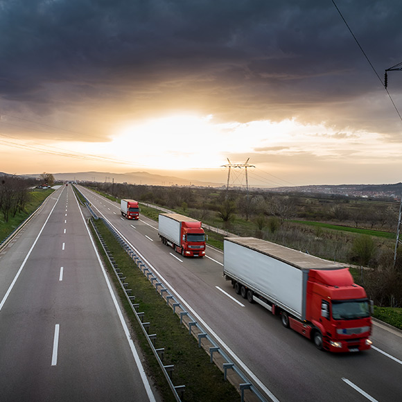 Three lorrys driving on near empty motorway