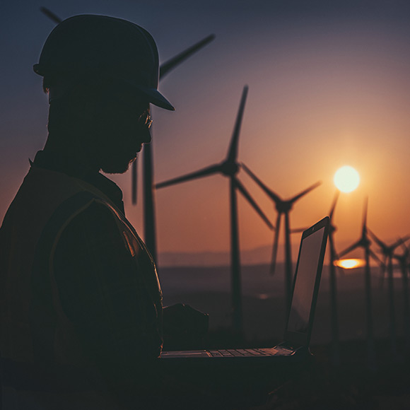 Construction worker using laptop with wind farm in background at sunset