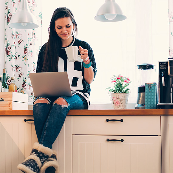 Young woman on laptop in kitchen
